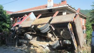 Freni boşalan kamyon, otomobil ile eve çarpıp devrildi