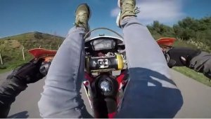 Motosiklete sırtüstü uzanıp tek tekerlek üzerinde gitti