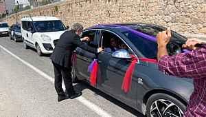 Davet edildiği düğüne yetişemeyen belediye başkanı, konvoyun önünü kesip takısını taktı