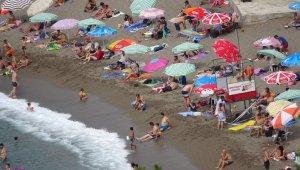 Sıcak havada plaja akın ettiler, ipte sosyal mesafeyi korudular