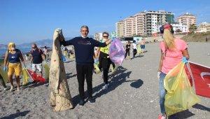Alanya'da yaşayan yabancılar bu defa mayoları ile değil çöp torbalarıyla sahile akın ettiler
