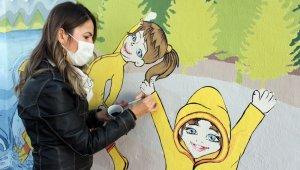 Şengül öğretmen çocuklar için duvarları renklendiriyor