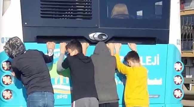 Halk otobüsünün arkasında çocukların tehlikeli paten yolculuğu
