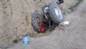 Devrilen traktörün altında kalan 2 kişi yaralandı